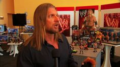 Triple HHH Checks Out His New Figure From Mattel At The 2010 New York To...