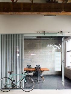 Meeting room name. Glass wall and simple wood conference table + HM chairs.