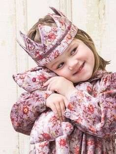 Somewhere, there is a precious little munchkin who will soon be melting hearts and spreading smiles at your most important events for the season. The Soiree is a real treasure trove of darling design; beautiful floral on antiqued amethyst velvet adorned with patch pockets and an adorable shawl collar with ruffle.