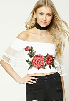 A knit crop top featuring an off-the-shoulder neckline, a large front embroidered floral patch, short sleeves with tiered flounce layers crafted from sheer mesh and piped edges, and an exposed back zipper.