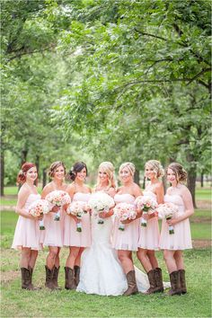 A stunning blush pink & ivory wedding with rustic details and full floral ceremony arch. The bride wore a strapless mermaid lace gown and the bridesmaids wore short, strapless blush pink dresses and cowgirl boots. The wedding bouquets were made with pink, peach and ivory roses and lace wrap - Photos by Drew Brashler Photography