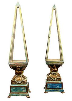 """Unusual pair of display cabinets or vitrines in the shape of obelisks. Base includes drawer and carvings of Roman armor and dates in Roman numerals. Bases rest on four small turtles. Vitrines are four sided, pointed at the top and have one glass shelf in the middle.  Width: 17""""    Depth: 17""""    Height: 76"""""""