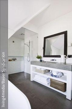 Der weiße Waschtisch mit grauer Steinplatte ist mit Regalfächern ausgestattet. So lassen sich Badutensilien ideal verstauen. In die ebenmäßige Steinplatte ist das Waschbecken eingelassen – das sorgt für einen modernen Look und ist gleichzeitig pflegeleicht. In Form einer ebenerdigen Dusche wird der geradlinige Stil fortgeführt.
