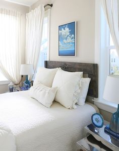 This small coastal bedroom is beautiful, airy, and serene. Coastal wall art and glass lamps bring the deep blue of the ocean to the space. Featured on Completely Coastal.