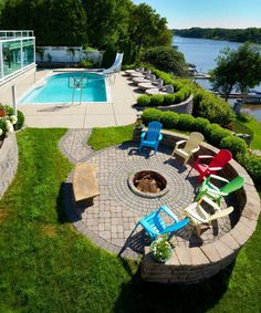 60 Backyard and Patio Fire Pit Ideas (Different Types with Photo Examples) Overhead view of a dog and wood-burning round fire pit in the centre of a brick patio surrounded by colourful Adirondack chairs over looking a pool and a river. Fire Pit Area, Diy Fire Pit, Fire Pit Backyard, Fire Pits, Fire Pit Near Pool, Backyard Kitchen, Backyard Pool Landscaping, Backyard Pool Designs, Backyard Ideas