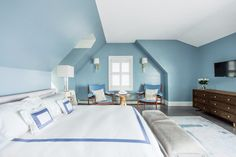 A charming blue attic bedroom with white and blue tones, comfortable bedroom bench and a pair of beach-like chair.