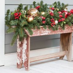 Rustic wooden bench near the front door decorated with greenery and ornaments.
