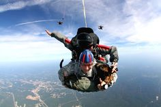 U.S. Army 1st Sgt. Chris Lalonde, center, holds his military working dog, Sgt. Maj. Fasco, and jumpmaster Kirby Rodriguez behind them, as they free fall through the air making history with the military's first tandem airborne jump from an altitude of 12,500 feet on Fort Leonard Wood, Mo. Sept. 18, 2009. Lalonde is assigned to Company D, 701st Military Police Battalion, and Rodriguez is assigned to the 342nd Training Squadron. U.S. Army photo by Sgt. Vince Vander Maarel
