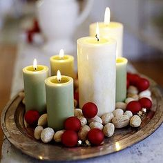Natural Light   Nestle soft-color candles in a bed of mixed nuts and tiny red ornaments set on a tray for easy ambience.