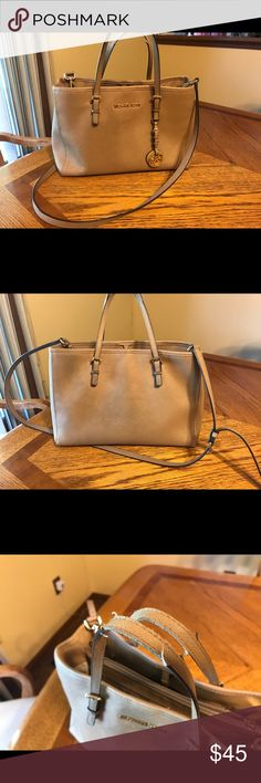 Michael Kors purse Tan color  •  Top Handle Bags  •  Two handles  •  Detachable shoulder strap  •  Two Compartments and Central Zip Pocket  •  Metal logo on front  • HEIGHT: 23 cm  • WIDTH: 15 cm  • LENGTH: 32 cm.  Handles are frayed and small lipstick stains inside middle zipper area but lots of life left. Michael Kors Bags Shoulder Bags