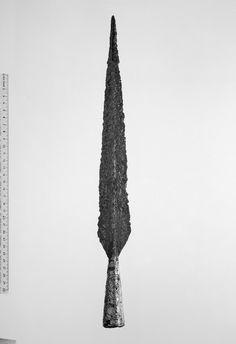 Rautainen keihäänkärki, jonka varsiputki on hopealevyin ja siinä näkyvin ornamentein koristeltu. Löydetty  muinaislinnan alapuolella sijaitsevasta Rapola...