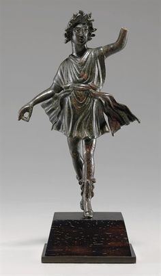 A ROMAN BRONZE DANCING LAR[Lares (singular Lar) were guardian deities in ancient Roman religion. Their origin is uncertain; they may have been hero-ancestors, guardians of the hearth, fields, boundaries or fruitfulness, or an amalgam of these.] CIRCA 1ST CENTURY A.D.