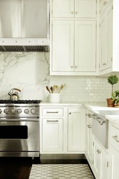 Love the accent marble piece behind the range. White kitchen.