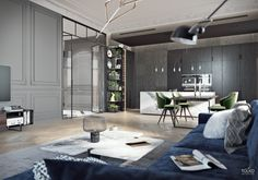 White marble block kithen island with an extension. Dark and grey wood living room. Grey panelled and glass walls. Dark blue and green furniture. Dark blue velvet couch.