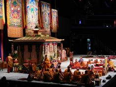 Tibetan Buddhist monks of the Gelugpa order pray and make offerings in front of the Kalachakra Pavilon, thankas of Kalachakra, Lord Buddha, mandala, Verizon Center stage, throne, drums, silks, decorations, Kalachakra for World Peace, Washington D.C., USA
