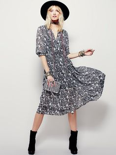 Butterfly Maxi Dress | In an allover butterfly print this sheer maxi dress features button closures down the front and a drawstring waist with hip pockets.  Three-quarter length sleeves with and elastic band at the cuff with ruffle detailing.  Lined with a half slip.