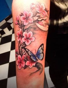 Beautiful pink-ink cherry blossom and blue-ink butterfly tattoo on arm