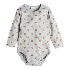 Body med knäppning vid axel och i grenen för enkel påklädnad. Guldtryck fram eller guldfärgade prickar på grå modell. Mjuk och skön bomull.
