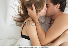 Overhead close up portrait of a young couple caressing laying in bed together in lingerie being romantic hugging and kissing. Couple in a relationship having sex in white bed, home interior lifestyle.