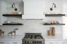Open shelves in dark wood, white Calcutta marble backsplash and library sconces give this updated kitchen a fresh farmhouse look, designed by Lindye Galloway.
