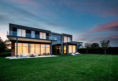 """OneButton recently outfitted a modern home on Long Island with smart lighting systems. """"The design theory for the space is an artistic minimalism that provides warmth and invites the beauty of the natural space indoors,"""" states the firm.  Courtesy of OneButton."""
