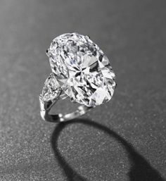 AN IMPORTANT DIAMOND RING, BY GRAFF  Set with an oval-shaped diamond, weighing approximately 26.24 carats, to the pear-shaped diamond shoulders, weighing approximately 1.06 and 1.04 carats, mounted in platinum,ring size adjustable 5¼ to 6¾ Accompanied by report no. 2155259755 dated 13 February 2013 from the GIA Gemological Institute of America stating that the diamond is D colour, VVS1 clarity, a working diagram indicating that the clarity of the diamond might be potentially Internally…