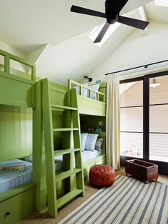 Fun attic bunk room with vaulted ceilings featuring skylights and modern bronze ceiling fan over sliding steel doors dressed in ivory curtains leading to an adjoining patio area.