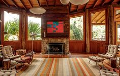As pedras brutas da lareira são exceção na casa de madeira feita pelo arquiteto Carlos Motta. Ela aquece o canto do living, já que o centro conta com um fogão a lenha