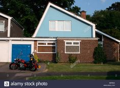 Download this stock image: 1960s suburban house Waterlooville, Portsmouth Hampshire UK with large red motorbike in front of garage in drive. - B6P8E4 from Alamy's library of millions of high resolution stock photos, illustrations and vectors.