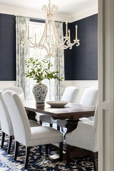 White and blue dining room boasts a blue floral rug placed beneath white and blue striped dining chairs placed around a dark brown wooden dining table lit by an Oslo Chandelier.
