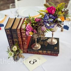 Vintage book and floral centerpieces // Sara & Rocky Photography // Flowers: Annie's Garden // http://www.theknot.com/weddings/album/a-vintage-wedding-in-normangee-tx-85376