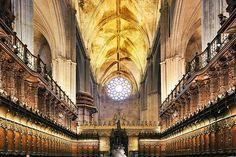 Catedral de Santa María de la Sede de Sevilla. Es la catedral gótica cristiana con mayor superficie del mundo. Según la tradición, la construcción se inició en 1401, aunque no existe constancia documental del comienzo de los trabajos hasta 1433. Obra del siglo XV, majestuoso templo de cinco amplias naves.La edificación se realizó en el solar que quedó tras la demolición de la antigua Mezquita Aljama de Sevilla, de la cual se conservan el alminar (la Giralda) y el Patio de los Naranjos.  Coro