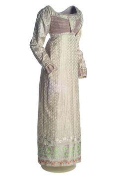 Vestido Neoclasicismo, ca. 1815-1819 Vestido en seda labrada en color beige, lila, verde, blanco y salmón. Con escote redondo, talle por debajo del pecho y manga muy larga. La base de la falda va decorada con un ancho zócalo de flores. MT016589