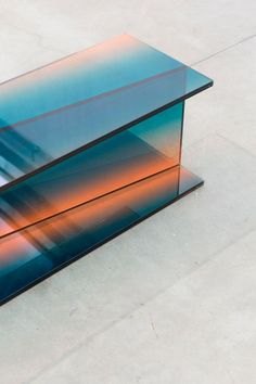 Designer: Germans Ermičs. Project: Shaping Colour. Exploring glass as a prominent material used in our everyday surroundings, like architecture, interior design, and furniture design. Aim to explore depth and softness, both of which are not thought of when it comes to glass. Using glass layering and printing techniques - results are a sculptural console,mirror and table.