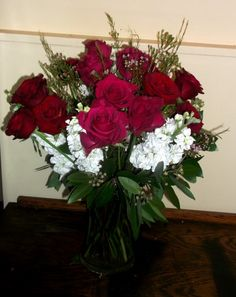 18 Hot pink and red roses are accented with pink wax flowers and white stock to create this arrangement that's romantic enough for your girl or sweet enough for your mom. $85.00