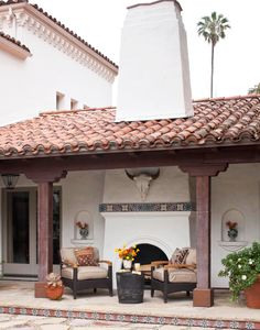 A tiled mantel continues the Spanish theme of the white stucco and red tile roof.