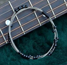 Recycled Guitar String Bangle with Black Glass Beads Gift for Musician or Music Lover. $20.00, via Etsy.  i want to make it!!!