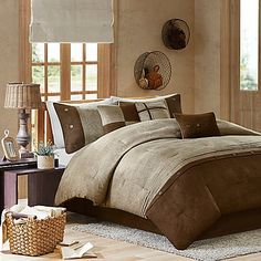 Create a warm look and feel with the rustic Madison Park Boone 7-Piece Comforter Set. The lodge-inspired bedding features a textured earthy print pieced with micro suede at the bottom and buttons accents in chocolate brown and tan hues.