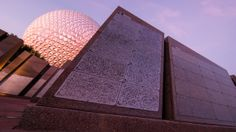 Two 'Leave a Legacy' stone monoliths with iconic Spaceship Earth in the background at Epcot