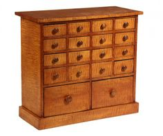 """Tiger Maple Veneer, pine secondary, with overhanging top, four banks of four small drawers over two large drawers, contrasting mushroom knobs, on plinth base. 28 1/4"""" x 31 1/4"""" x 13"""""""