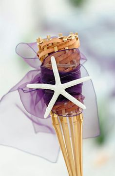 Close up of a tropical tiki at a Suncoast Wedding with an eggplant sash and a stark white starfish .. beautiful!