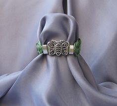 https://flic.kr/p/VBBvNN   CELTIC KNOTS   Women's bracelet made of light green metallic leather cord ,with silver plated zamak accessories and magnetic clasp.