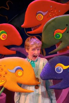 Context is needed.  Why is this boy in the middle of a group of large fake fish?  Is it a musical or a tv show perhaps? low cognitve thinking