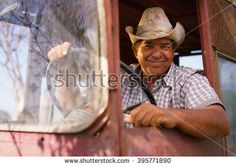 Farming and cultivations in Latin America. Portrait of middle aged hispanic farmer sitting proud in his tractor at sunset, holding the steering wheel. He looks at the camera and smiles happy. - stock photo