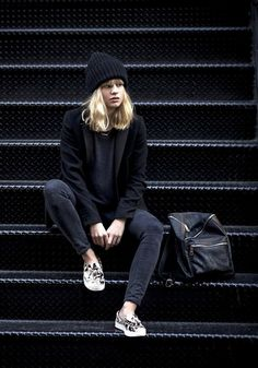 Lisa Dengler wears a blazer, black separates, a beanie, and printed sneakers