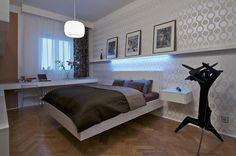 Také v ložnici je zachován koncept celého bytu. Bílá barva je doplněna zajímavou tapetou. Ani tady nábytek nestojí na podlaze.