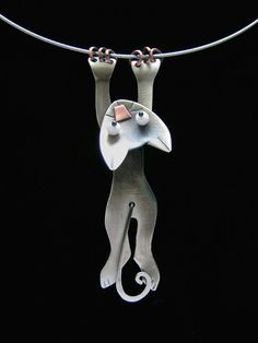 Hang In There Necklace by Lisa And Scott Cylinder. Antiqued Nickle Silver, glass beads, copper. Body and tail swing. Cat moves freely on cable. Fabricated and silver soldered. 18 magnetic closure stainless steel cable. Dimensions refer to pendant size.
