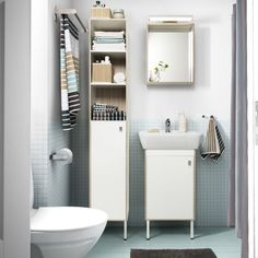 A small bathroom with light blue floor tiles, a white high cabinet, a mirror and a wash-basin cabinet. Combined with striped towels in light blue, beige, brown and white.