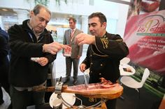 Photo: Food writer / Catalan culinary personality Xavi Agullò takes a fresh-cut piece of jamón Ibérico from champion cortador de jamón Clemente Gómez at Los Pedroches jamón Ibérico stand, on a jamón stand hopping tour that I organized at Madrid Fusión 2014.  Photo by Gerry Dawes©2014 / gerrydawes@aol.com / Facebook / Twitter / Pinterest.  Canon 5D Mark III / Tokina 17-35mm f/4.