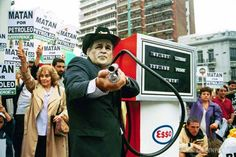 """2003. Campaña contra la Guerra del Golfo. Un activista caracterizado como George W. Bush, en ese momento presidente de Estados Unidos, sostiene la manguera de un surtidor de combustible que simula ser un arma. Con esta acción denunciamos que el motivo real de la guerra en medio oriente era """"matar por petróleo"""".    © Greenpeace"""